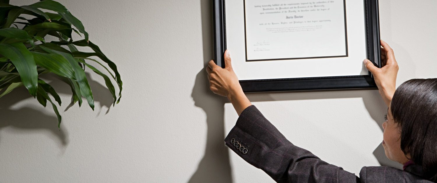 Woman hanging certificate in her office
