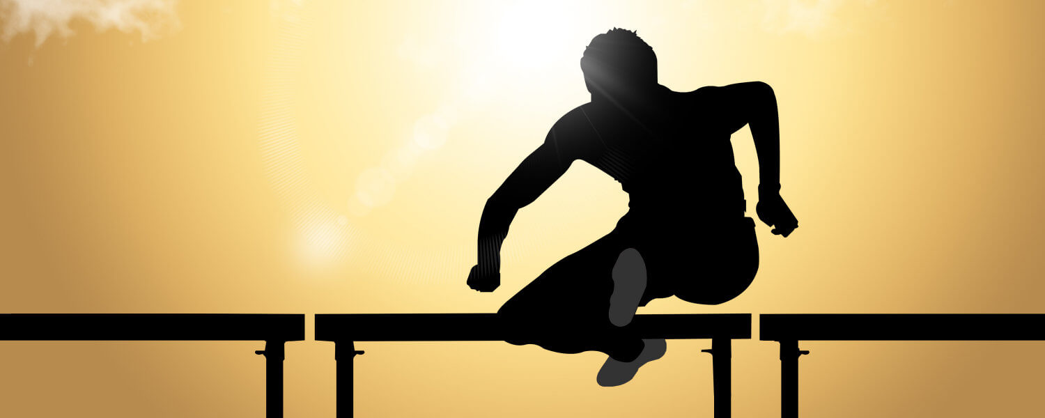 Person jumping a hurdle, shown backlit